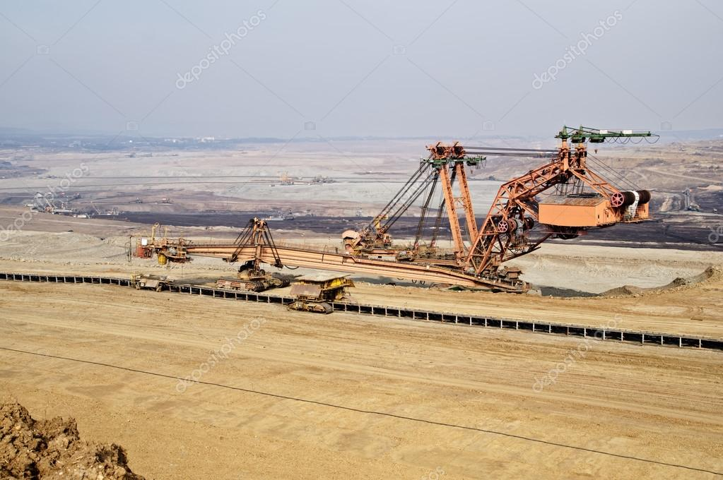 Giant mining excavator on the bottom surface mine. Brown coal deposits.