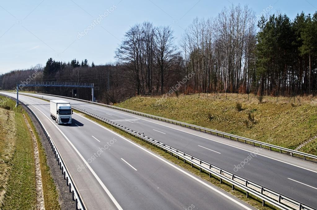Motorway around the woods in early spring. White truck under electronic toll gates.