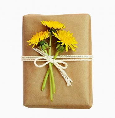 Package wrapped in paper and tied with a rope and flowers