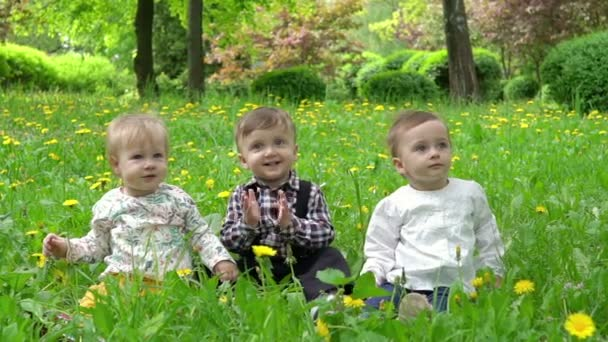 Tři děti na trávě, na kterém lístky padají ze stromů, zpomalené