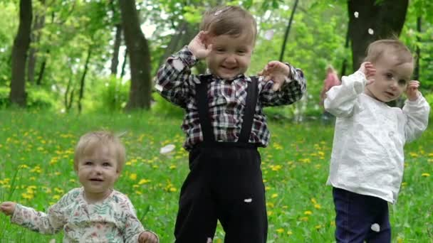 Három gyermek a füvön, amelyen a szirmok hullanak a fák, lassú mozgás
