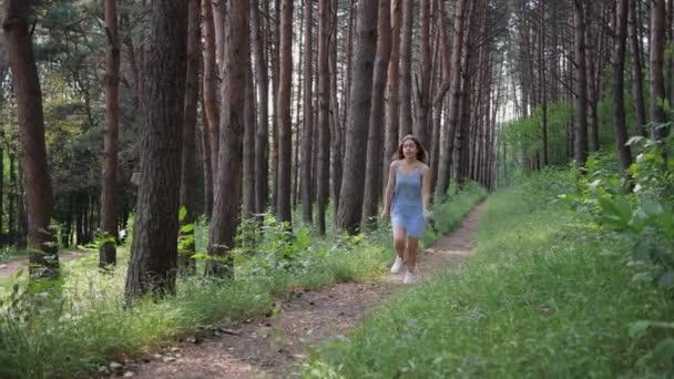 Mladá krásná romantická žena v modrých šatech běží s kyticí divokých květin podél cesty v parku nebo lese. Zpomalený pohyb