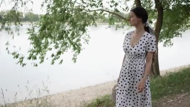 Young beautiful woman in white dress walks along lake in Park. Summer