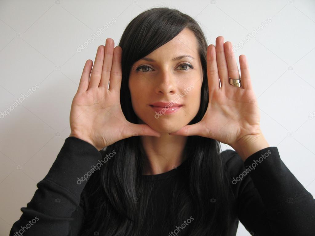 Chica guapa Marcos cara con las manos — Fotos de Stock © mbudley ...