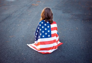 Sad lonely patriot woman sitting down with the american flag wra