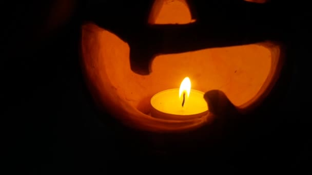 Lighted pumpkin-shaped candle for halloween burning