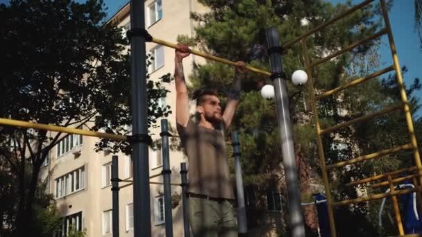 Sportovní aktivity na venkovním pozemku a zdravý životní styl. Fitness a silová cvičení pro svaly paží. Svalnatý běloch s plnovousem se oběma rukama vytáhne na vodorovnou tyč..