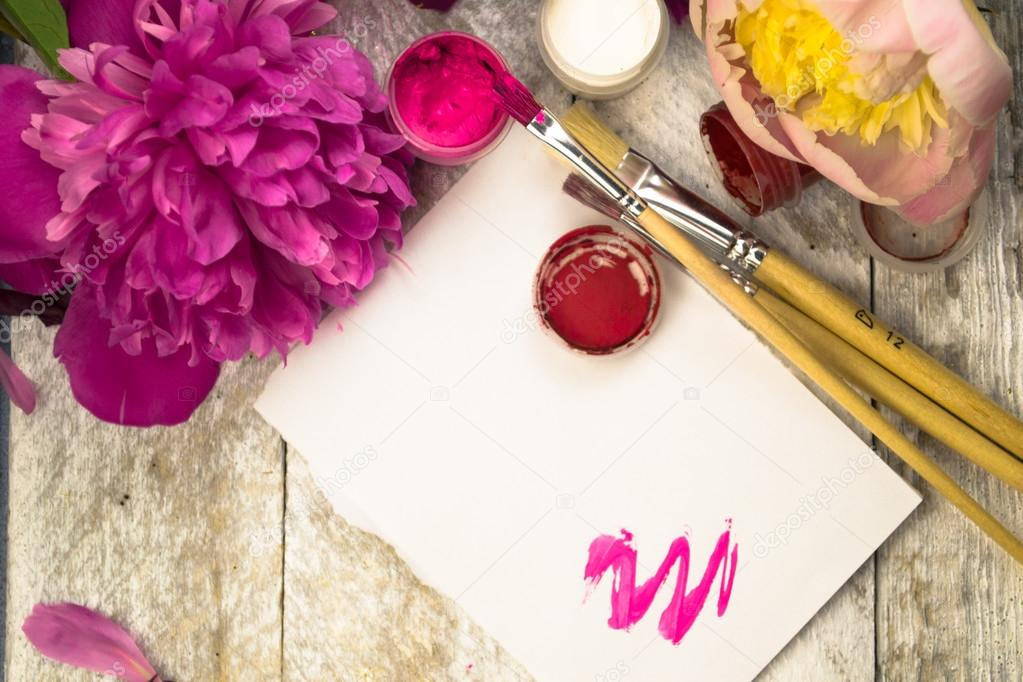 Workspace. Watercolor, paintbrush and pink peonies isolated on white background. Overhead view. Flat lay, top view