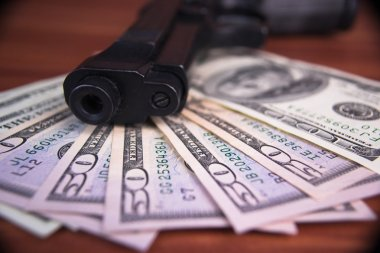 Gun, drugs and money on wooden background
