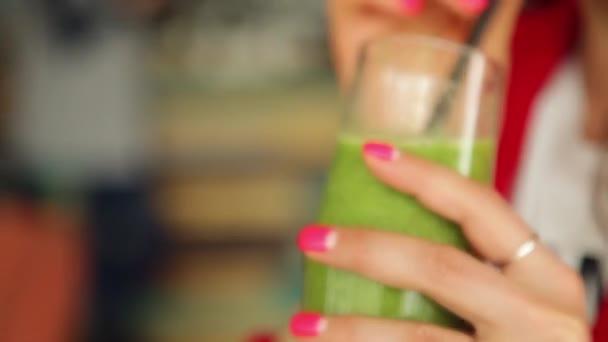 Holka pije zelený koktejly s ovocem a zeleninou