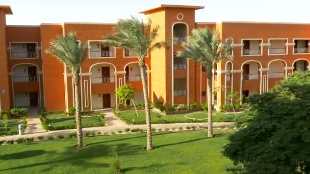 Vysokými palmami poblíž oranžové budovy. 4k