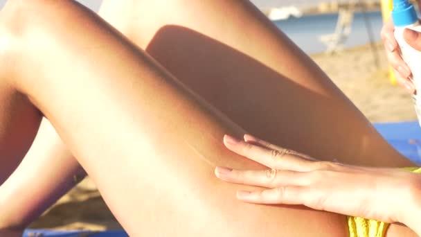 Krásná mladá žena použití opalovací krém na nohy na pláži. HD