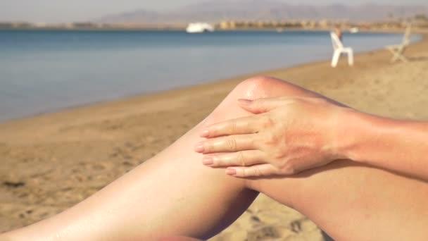 napvédő alkalmazása a lábak, a tengerparton a gyönyörű fiatal nő. HD