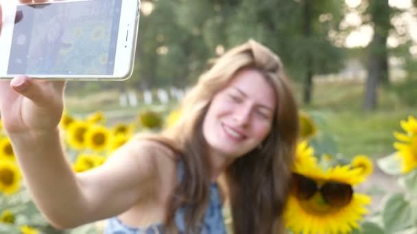 Young woman doing selfie near sunflowers. HD