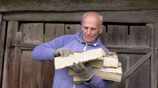 alter Bauer in Handschuhen stapelt hölzerne Feuerhölzer mit Händen im Freien