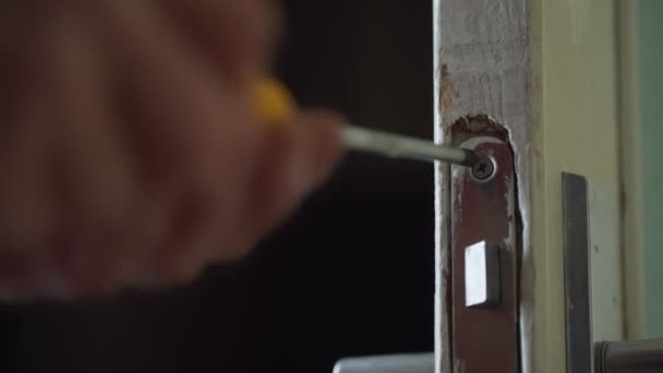 Male hand holds screwdriver and turns metal screw in door lock.
