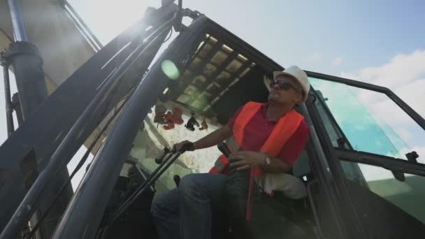 Bulldozer operator in white hardhat and orange vest seated in cabin
