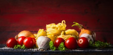 Pasta tagliatelle with tomatoes, herbs and spices for tomato sauce, comosing on dark red background, banner, top