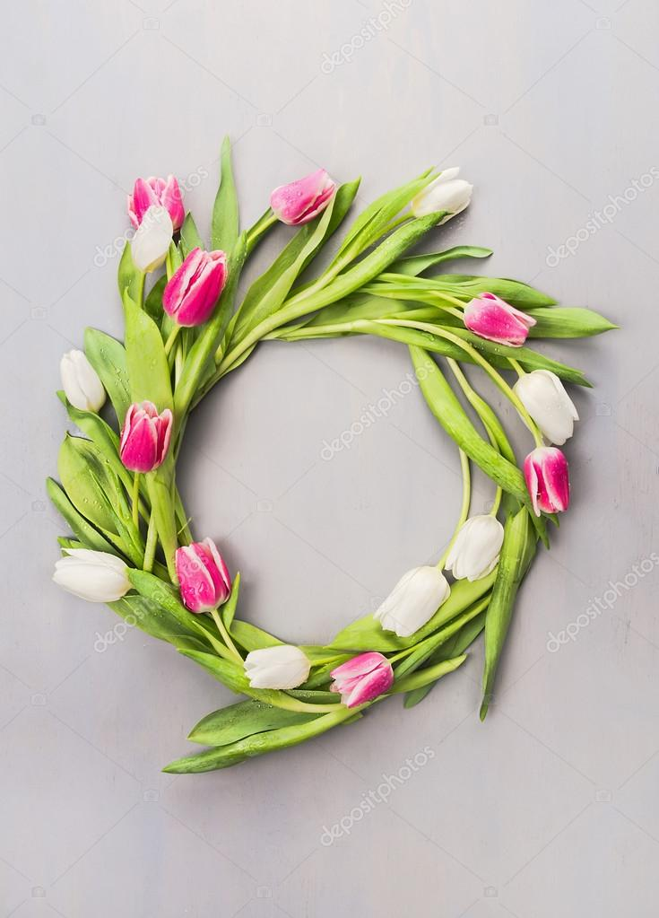 Wreath of pink and white tulips on a gray wall