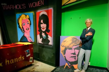 NEW YORK, CIRCA 2011 - Andy Warhol's wax figure with his pictures in Madame Tussaud's museum in New York