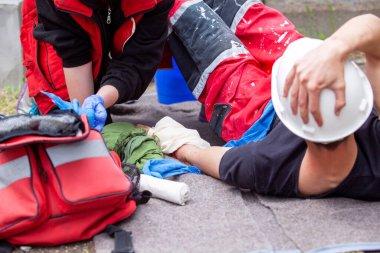 İnşaat alanında kazadan sonra ilk yardım. İş yerinde el yaralanması.