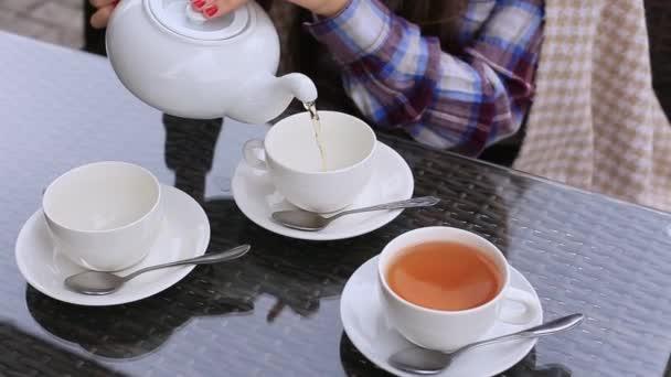 Žena nalévá čaj z sklenici do hrnku