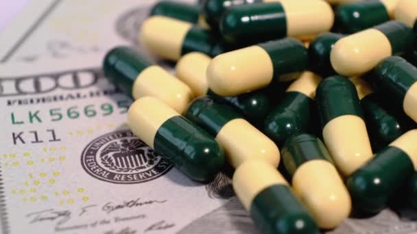American dollars banknotes and many medical pills in yellow green capsules on a rotating table. Pay money for treatment, medicines, vitamins, drugs.
