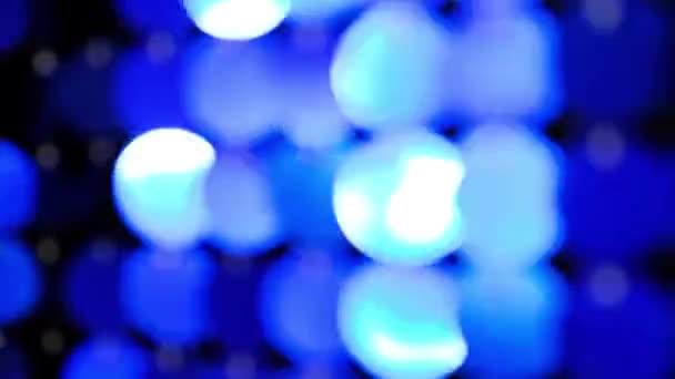 Abstraktní rozostřené třpytky blikající na modrém pozadí. Stěna zářící pohyblivé prázdninové dekorace.