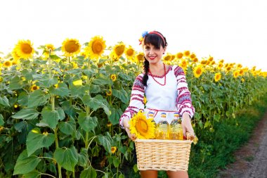 Smiling girl in embroidery holding a basket with sunflower oil