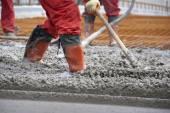 Fotografie Dělníci v červené boty s hrábě vyrovnání betonu