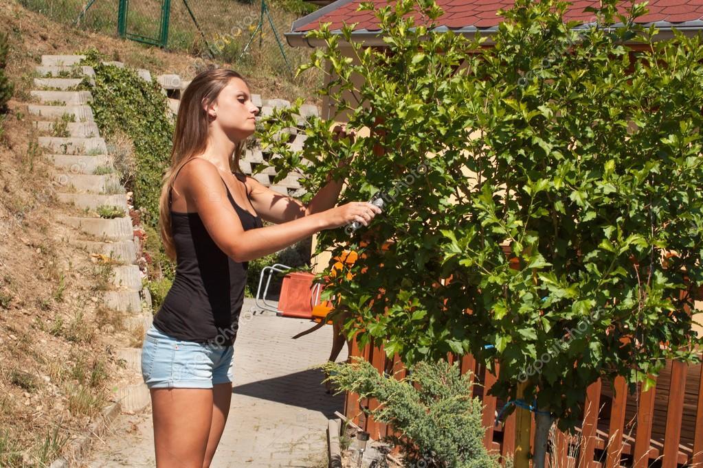 Beautiful girl working in the garden. Young gardener adjusts garden. Summer day in the garden.