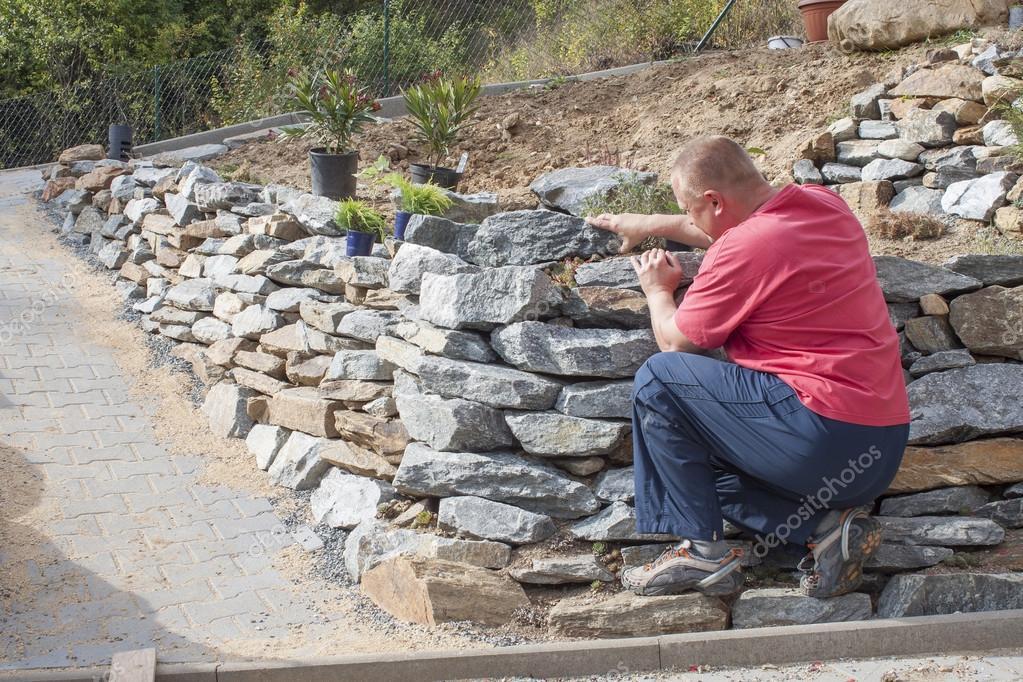 Stenen Muur Tuin : Tuinman bouwt een stenen muur tuin voorbereiding architect stelt
