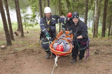 Pnovany, Czech Republic, June 4, 2014: training rescue injured people in difficult terrain at the dam, carrying a stretcher with an injured person