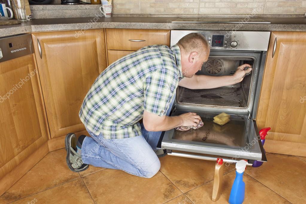 Mann Kniet Auf Dem Boden In Der Küche Und Reinigt Den Ofen.  Reinigungsarbeiten Im Haus. Mann Seine Frau Mit Aufräumen Helfen U2014 Foto Von  Marsan