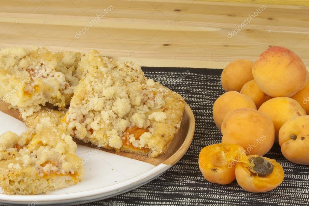 Homemade apricot cake on a plate. Freshly picked apricots on a wooden table. Homemade dessert of summer fruits.