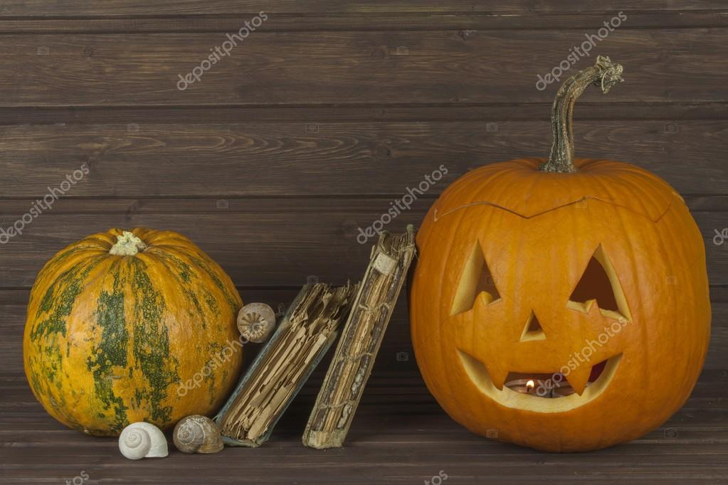 Halloween pumpkin head on wooden background. Preparing for Halloween. Head carved from a pumpkin on Halloween. Pumpkin tradition. The book of spells, magical book.  Textbooks for witches.