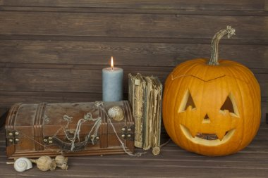 Finding a mysterious wooden box. Mystery enclosed in the cabinet. Retro look of ancient box like pirate treasure chest. Invitation for halloween. Scary Halloween pumpkin. The book of arcane magic
