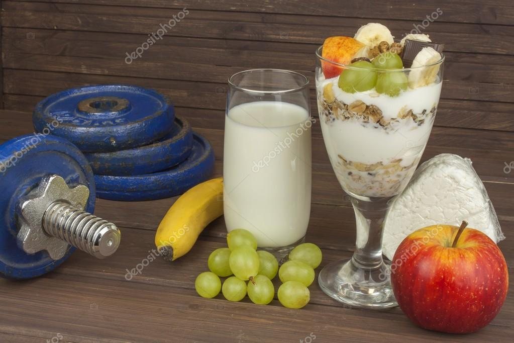 Diet for athletes build muscle mass. Protein snack. Dairy products and dumbbells. fresh milk in the glass and muesli breakfast on a wooden table. Oatmeal with milk and curd, meals for athletes