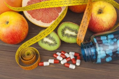 Dietary supplements for weight loss. Red grapefruit and fruit for weight loss. Fresh dietary food for athletes. Fruit on a wooden table.Balanced diet. Assortment of exotic fruits.