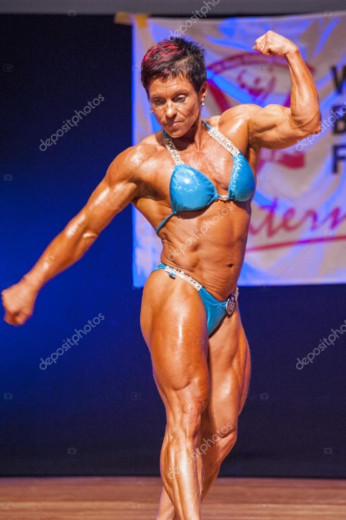 Bodybuilderin beugt ihre Muskeln um ihren Körper zu zeigen ...