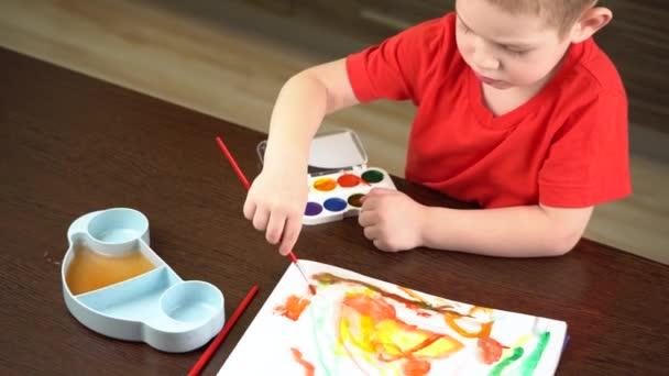 Kind im roten T-Shirt malt mit bunten Aquarellen am Tisch
