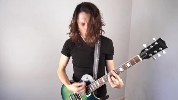 Mladík hraje na elektrickou kytaru a mává dlouhými vlasy. Emocionální výkon rock and roll