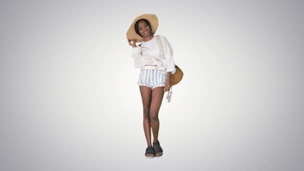 Usmívající se mladá africká americká žena v slaměném klobouku pózující na sklonu pozadí.