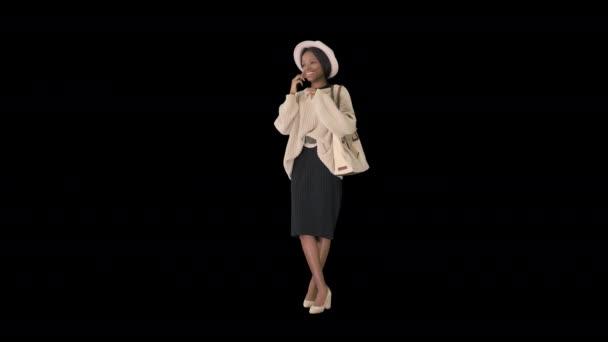 Usmívající se afro-americká žena v pletených šatech a klobouku mluví po telefonu, Alpha Channel