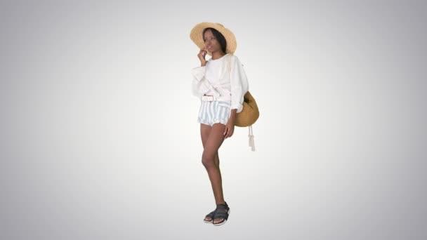 Krásná mladá africká americká žena v slaměném klobouku mluví na svém telefonu na sklonu pozadí.