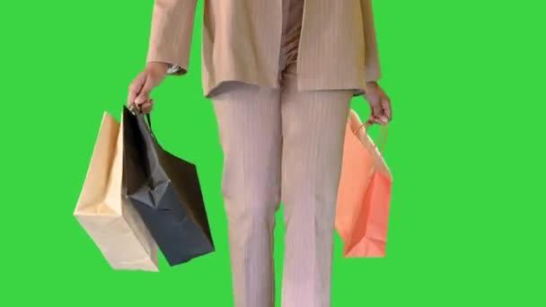 Bevásárlótáskák kezében sétáló afro-amerikai nő egy zöld képernyőn, Chroma Key.