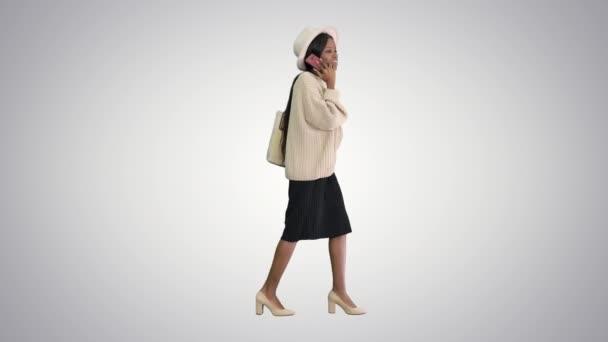Frustrierte Afroamerikanerin in Strickpullover und weißer Mütze telefoniert auf Steigungsuntergrund.