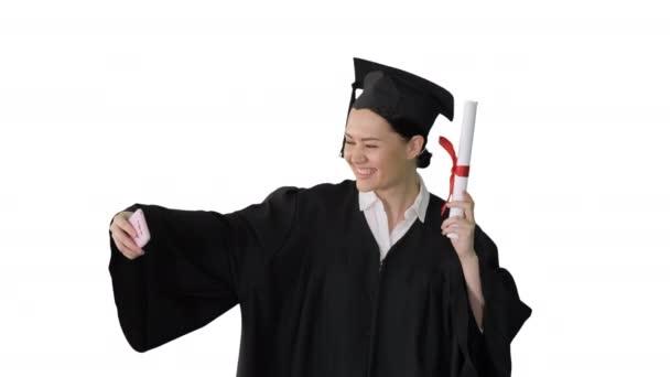 Boldog női diplomás gazdaság diploma és szelfi a telefonján fehér háttér.