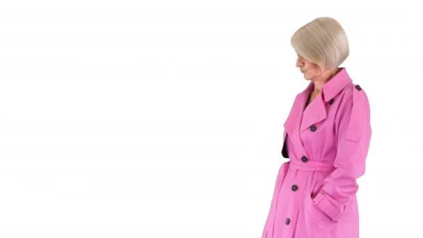Schöne Seniorin im rosa Herbst-Outfit auf weißem Hintergrund.