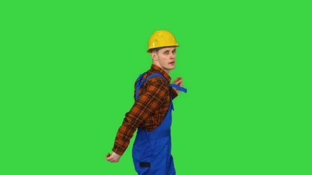 Tančící mladý inženýr s helmou po práci na zelené obrazovce, Chroma Key.